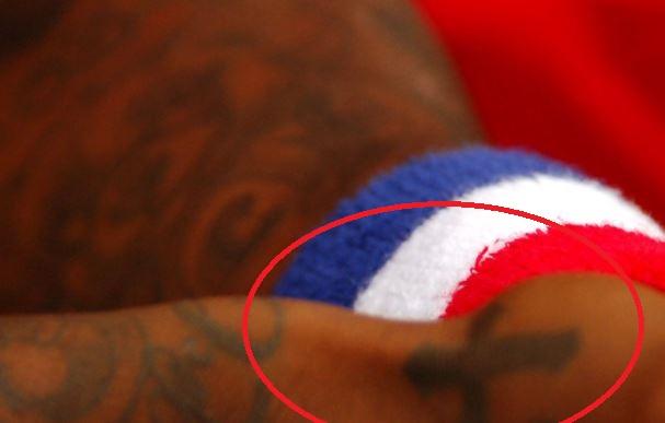 Djibril cross on hand tattoo