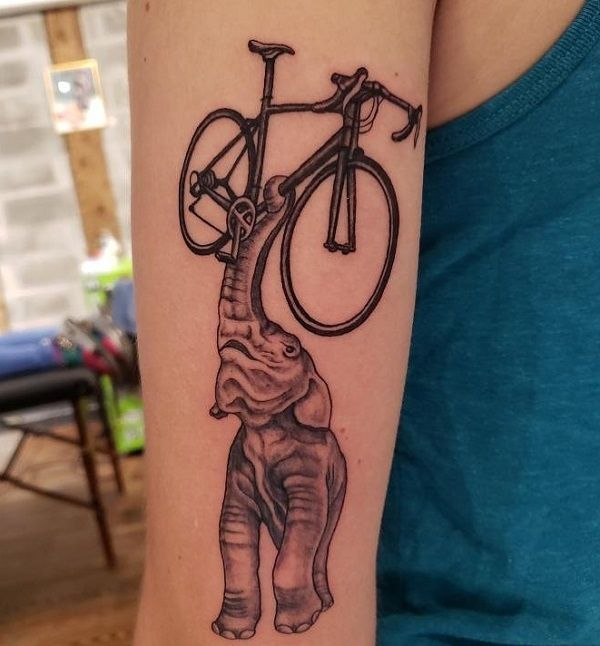elephant holding a bicycle tattoo