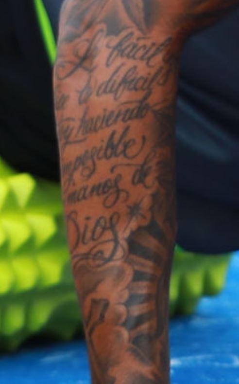 Javier writing on arm tattoo