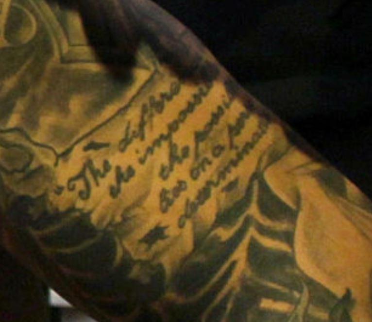 Aaron writing on bicep tattoo