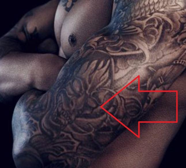 Courtney skull on arm tattoo