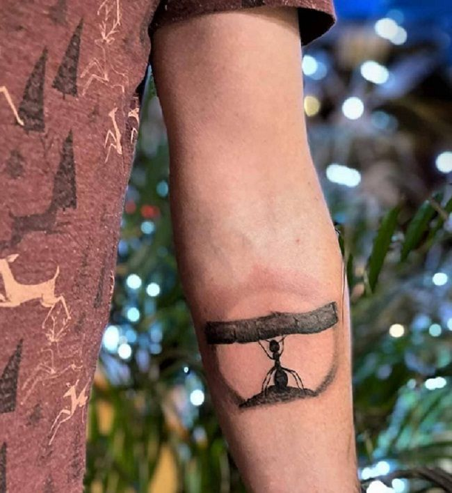 An Ant lifting a wooden branch Tattoo