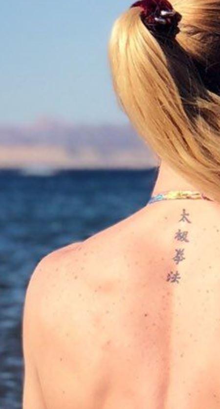 Valentina writing on back tattoo